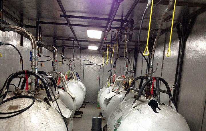 Urethane foam tanks in a heated tank storage room with a cascading feed system and ceiling pull values.